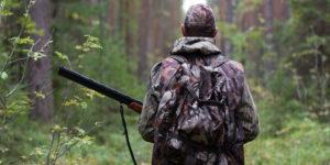 osoba stoąca tyłem ubrana na zielono z bronią, w tle las, drzewa
