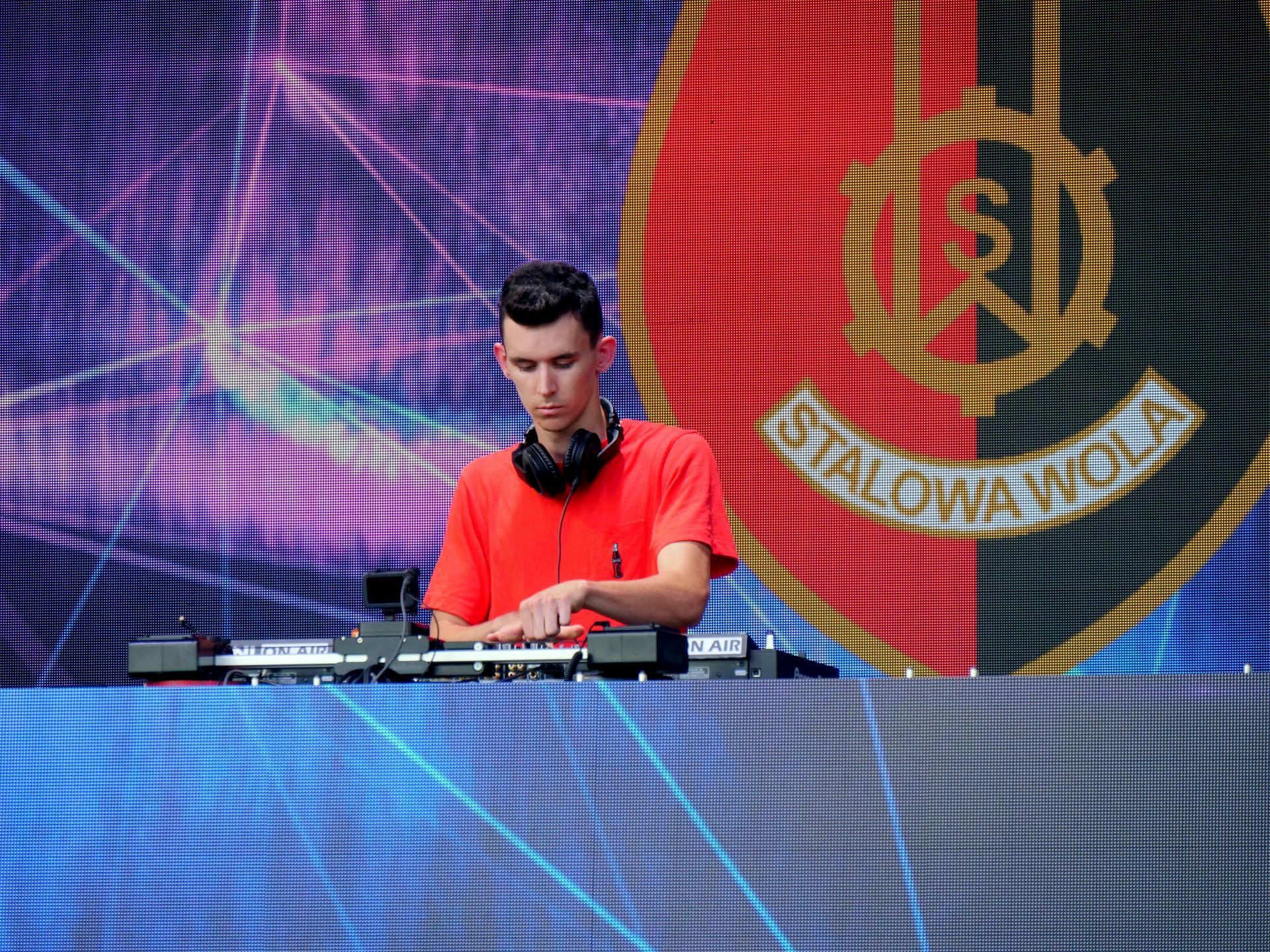 DJ Hertz za konsolą na tle herbu Stalowej Woli
