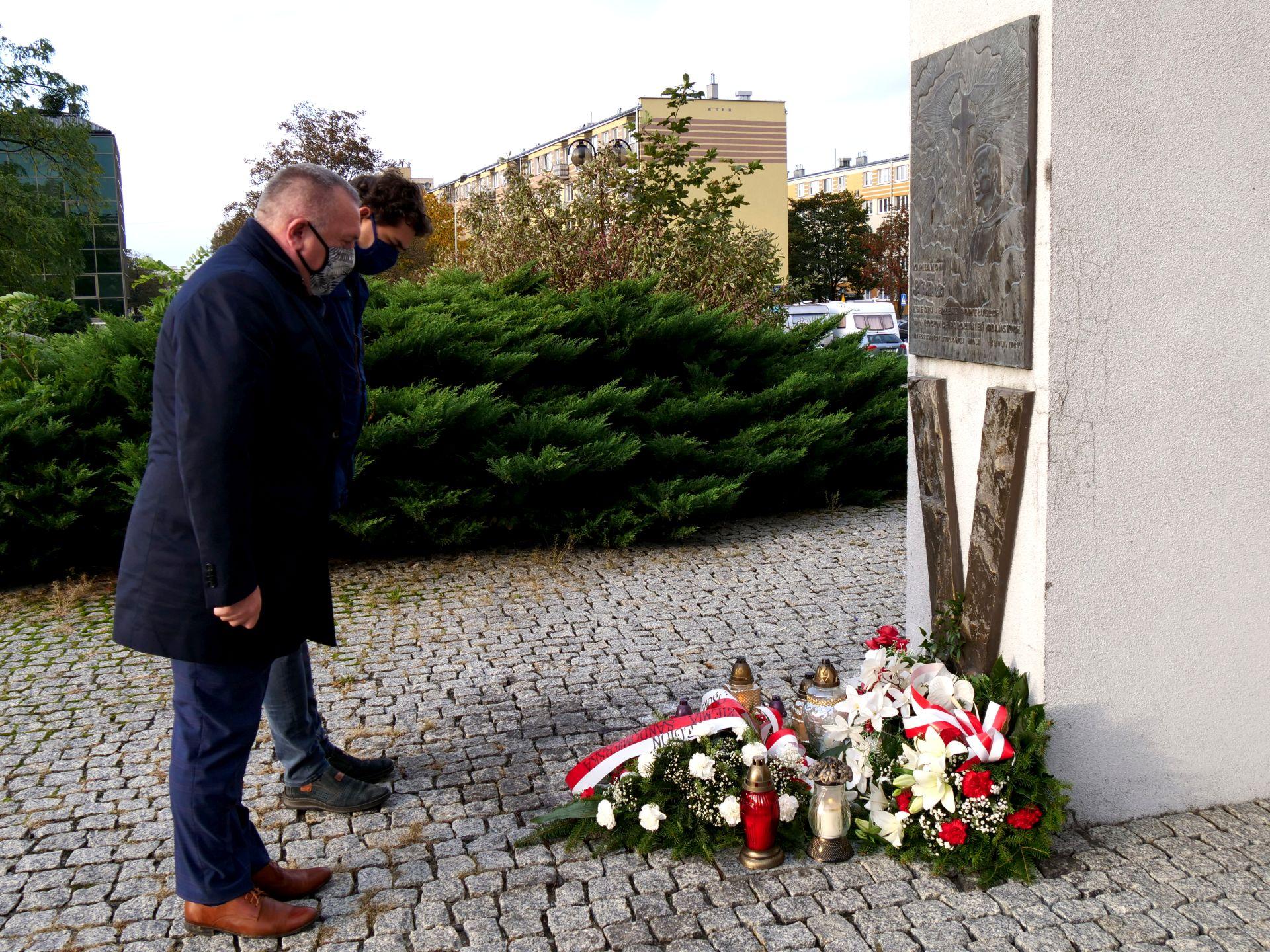 pomnik, dwie osoby, kwiaty