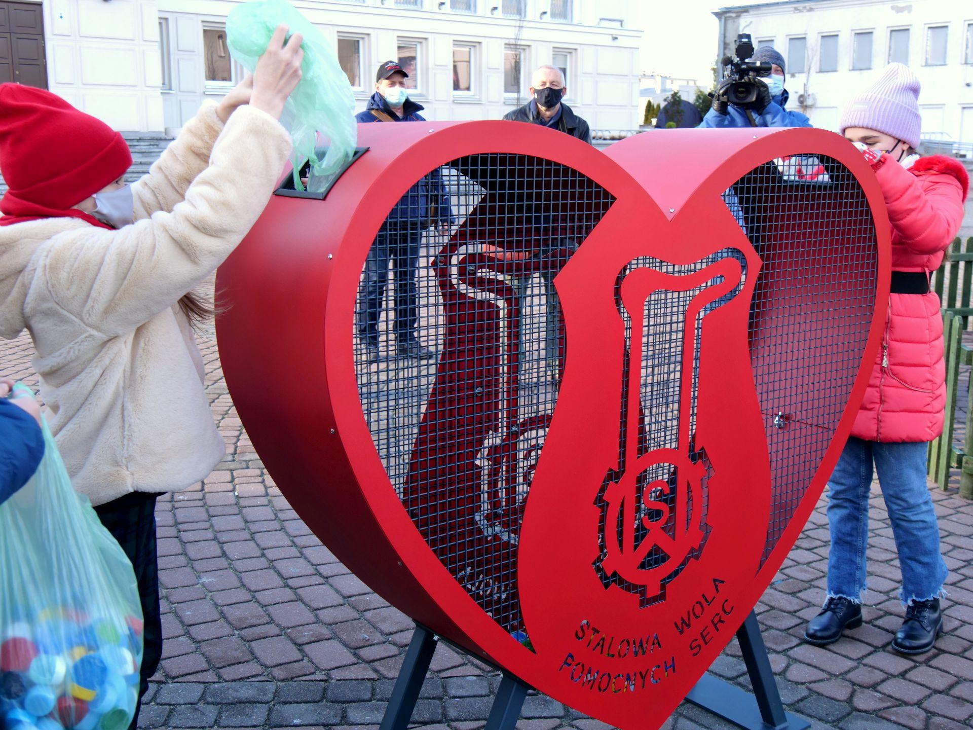 wiele osób, nakrętki, pojemnik w kształcie serca