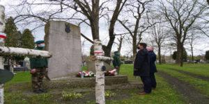 cmentarz, cztery osoby, drewniane krzyże, kwiaty.