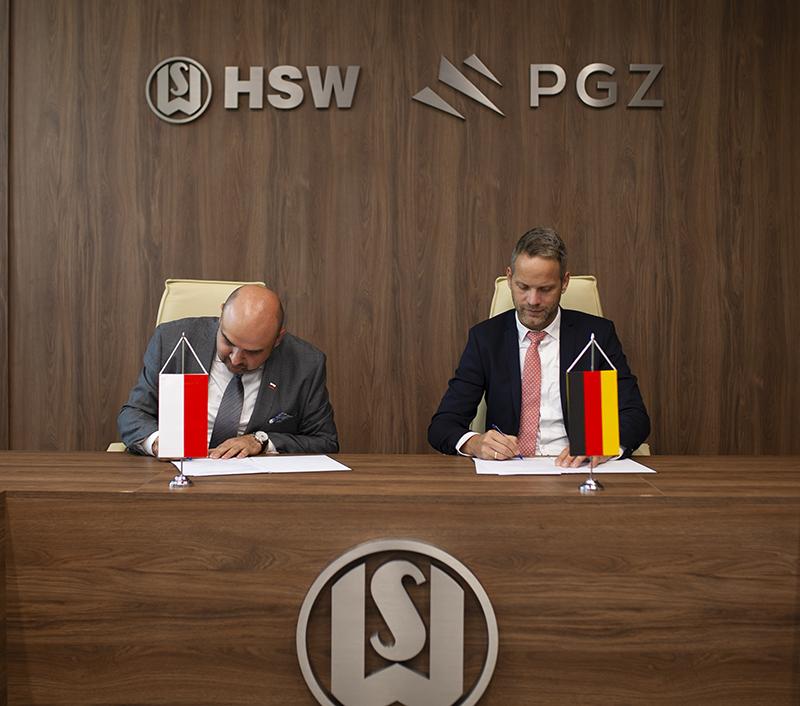 dwie osoby, podpisanie dokumentów, w tle logotypy