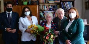 5 osób, 1 z kwiatami, w tle pokój i regał z książkami