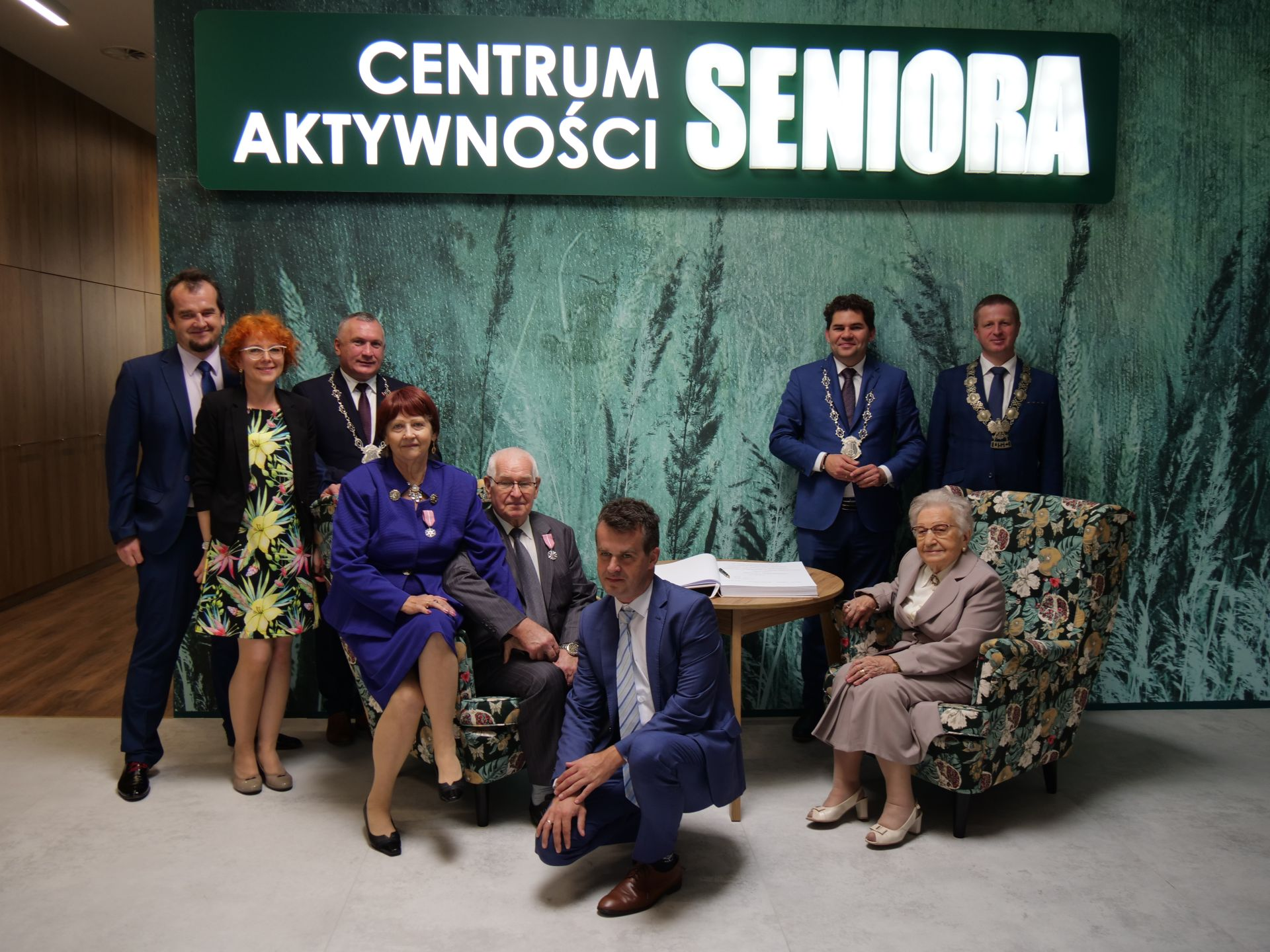 wiele osób: napis: Centrum Aktywności Seniora