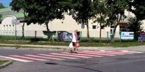 Jedna osoba na przejściu dla pieszych w tle budynek