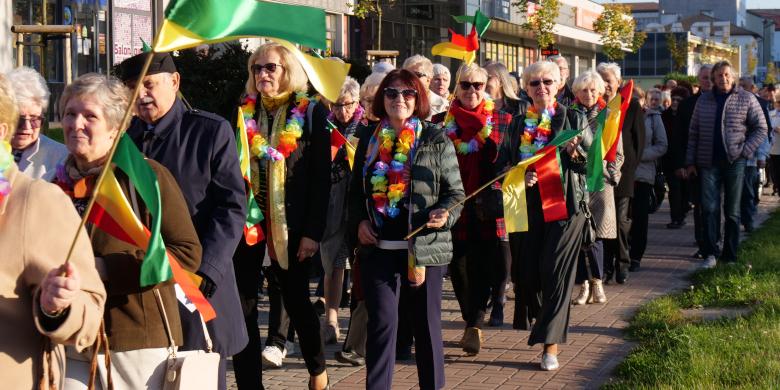 Wiele osób z kolorowymi flagami w tle chodnik i pawilony sklepowe